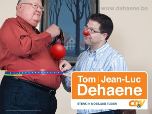 De centrale campagnefoto van JLD. Voor zoveel clowneske electorale navelstaarderij verdient hij een neus op die plaats. Of dient die dikke buik vooral om de aandacht af te leiden van zijn dikke portefeuille?