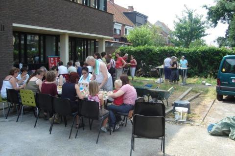 Zaterdag 27 juni, meer dan veertig vrijwilligers eten op de parking achter het nieuwe gebouw.